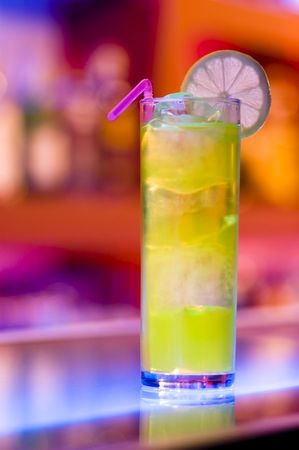 Colorful cocktail on a bar with blurry background