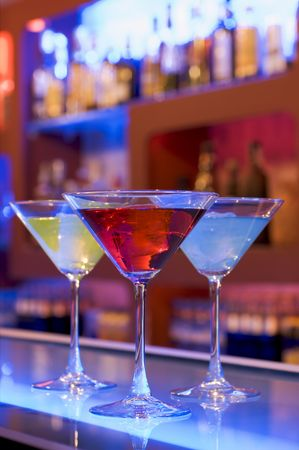 happyhour: cocktail drinks on a bar, blurry background with bottles