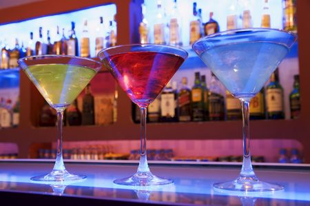 happyhour: blue, red and yellow cocktail drinks on a bar