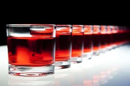 shooter: Several red alcohol shots on a bar.