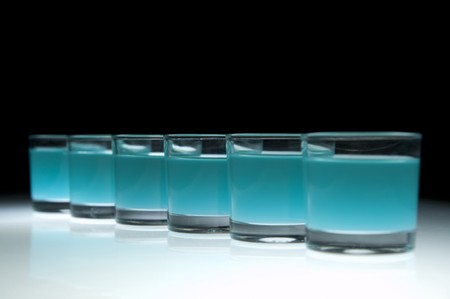 Six shot glasses filled with colored alcohol, black background.