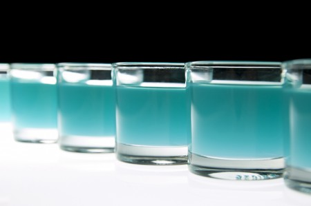 happyhour: Several shot glasses filled with colored alcohol, black background.