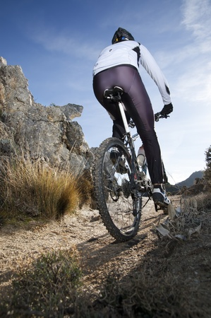 Man riding a mountainbike on a mountain track, view from behind photo
