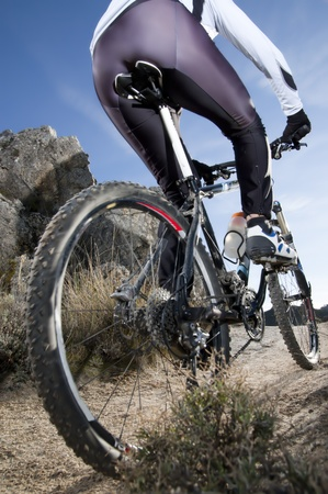 Man riding a mountainbike on a mountain track, close-up view from behind