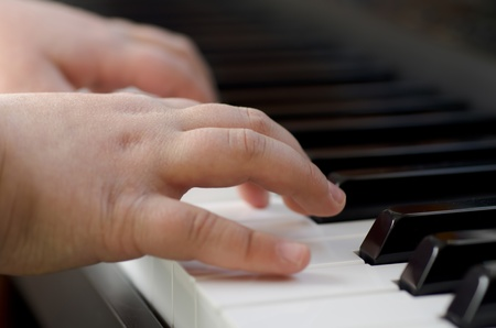 Closeup image of a child playing the piano photo