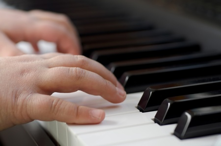Closeup image of a child playing the piano