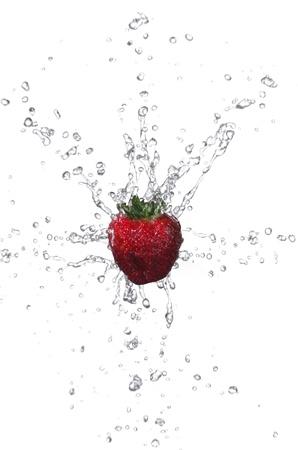 Fresh strawberry with water splashing on white background