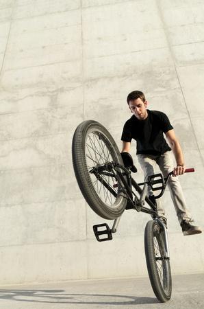 Jonge fietser op een grijze stedelijke betonnen achtergrond Stockfoto
