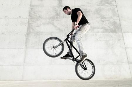 the rider: Bicicletta giovane pilota su uno sfondo grigio cemento urbano