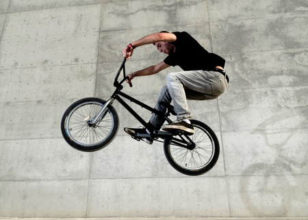 bmx bike: Young bicycle rider on a grey urban concrete background Stock Photo