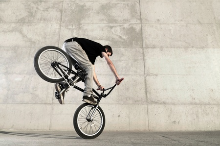 Young bicycle rider on a grey urban concrete background 스톡 콘텐츠