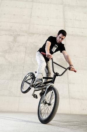 stunts: Bicicletta giovane pilota su uno sfondo grigio cemento urbano