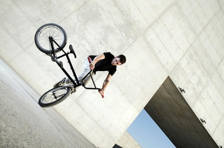 Young bicycle rider on a grey urban concrete background photo