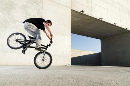 bmx: Young bicycle rider on a grey urban concrete background Stock Photo