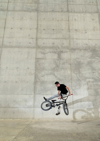Young bicycle rider on a grey urban concrete background Stock Photo