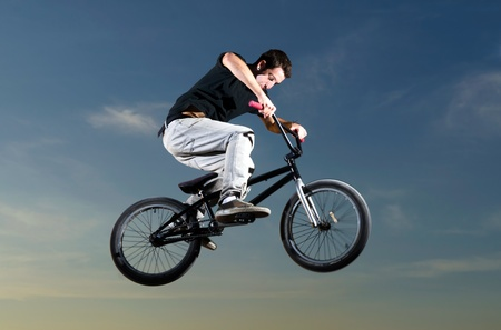 Young bicycle rider on a sunset sky background photo
