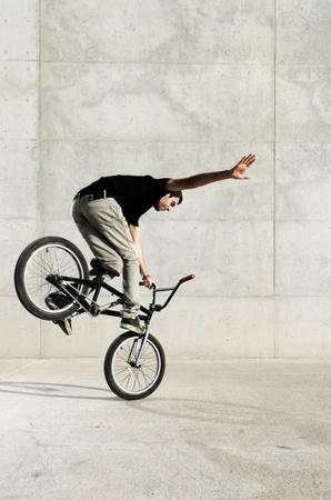trial balance: Joven piloto de bicicletas BMX en un fondo de hormig�n gris urbano