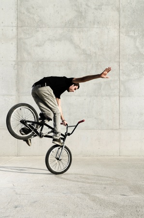 trial: Young BMX bicycle rider on a grey urban concrete background