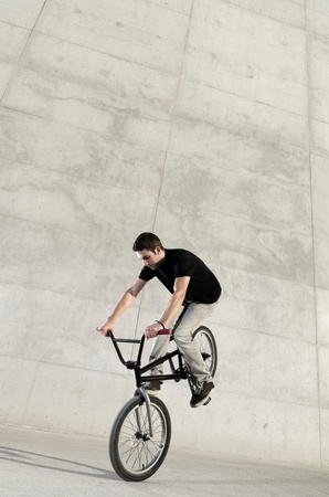 Young BMX bicycle rider on a grey urban concrete background photo
