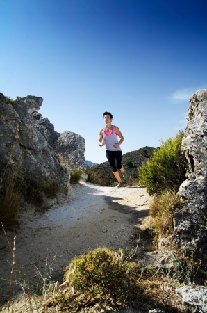 Young woman running on a mountain path. Stock Photo
