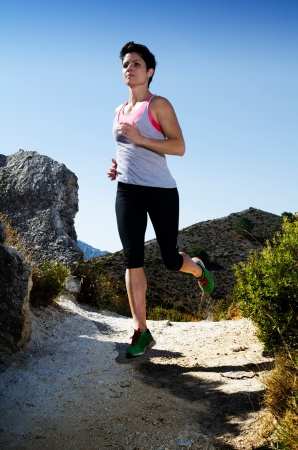 Young woman running on a dry mountain path. Stock Photo