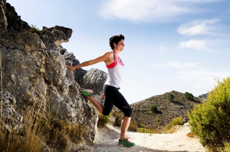 Young woman stretching on a dry mountain path.