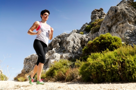 Young woman running on a dry mountain path. photo