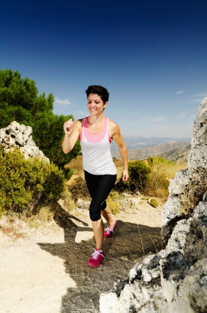 Young smiling woman running on a dry mountain path. Stock Photo