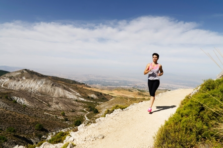 Young short-haired woman  running on a dry mountain path. photo