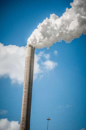 spewing: industrial chimney spewing smoke on blue sky