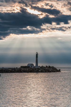 Lighthouse of Port-La-Nouvelle in red and white on cloudy sky in Occitanie, France Imagens