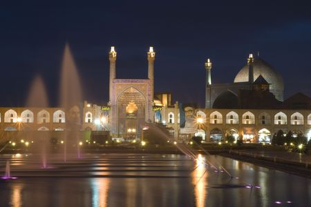 forground: Esfahan, Persia, winter 2009-night view on Imam Mosque in Esfahan. Water pool with many fountains and lights in forground.