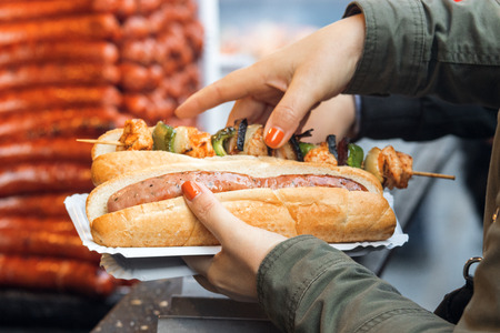 Woman bought her meal at Christmas street market. She holds paper tray in left hand, 2 breads on the tray, one with the sausage and  the other one with kebab skewer. Detail image, focus on 1st bread with sausage. Stock Photo