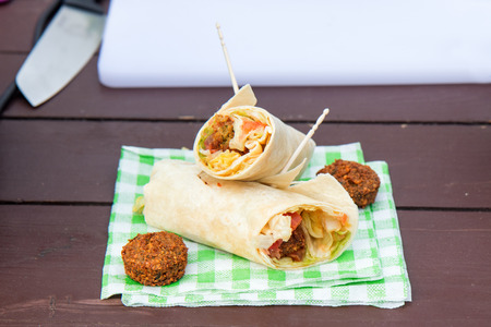 The street food, vegetarian vegetable wrap served on the paper napkin. The green letuce, tomato, onion and 2 pieces of chickpeas falafel. Stok Fotoğraf