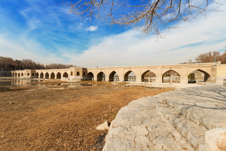 The view on almost dry riverbed of Zayandeh river flowing down in Isfahan city, Central Iran. Bright blue sky with some clouds over Chubi Bridge in winter season. Stock Photo