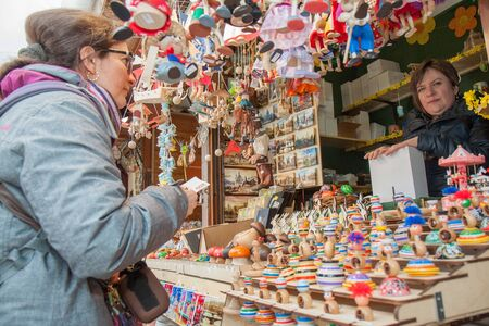 PRAGUE - APRIL 16th: Customer buys easter souvenir in the street market on Old Town Sq. on April 16th, 2017 in Prague, Czech Republic. Wooden toys like these do not belong among traditional Czech Easter decoration, but vendors from Ukraine try to sell any Foto de archivo - 128135949