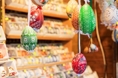 Wide selection of easter eggs, traditional souvenirs in the kiosk of street market during celebration of Easter in Central  Europe. Compartments full of colourfull eggs. Focus on green eggs.