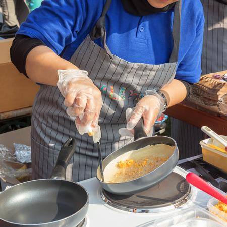 シェフはストリートフードマーケットプレイスでストリートフードイベント中にパンケーキのターンオーバーを行い、女性はトウモロコシとピーナッツスプレッドでパンケーキをひっくり返します。