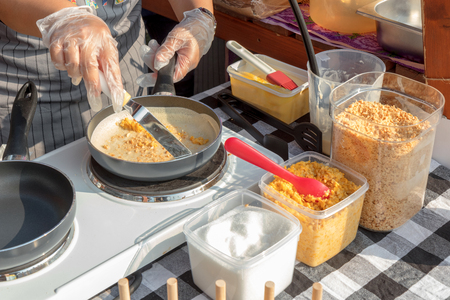 The chef makes pancake turnover during street food event at street food marketplace, the woman flips pancake with corn and peanut spread. Stock Photo