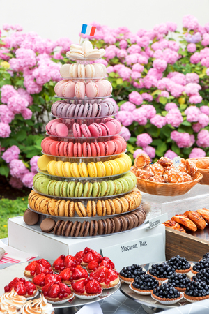 Variation of sweet pastry, pastry fruit bowls with blue berries, strawberries, raspberries, box with pyramid of macarones, basket with croissants, glass with brown sugar and other pastry.