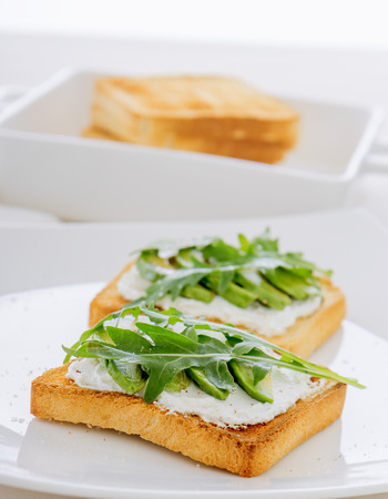 Roasted toasts with cream cheese and slices of avocado, leafs of rucola and pink Himalayan salt. Front view, low angle, focus on the centre of both breads. White wood background.