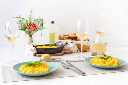 Risotto Milanese, wooden table with traditional Italian saffron risotto, glasses and pitcher of wine, bottle of olive oil, basket of bread and flowers, lunch for 2 people .