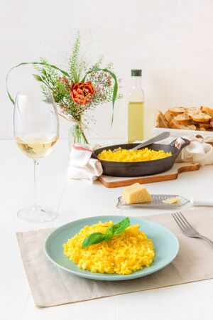 Risotto Milanese, wooden table with traditional Italian saffron risotto, glasses and pitcher of wine, bottle of olive oil, basket of bread and flowers, lunch for 2 people . Standard-Bild