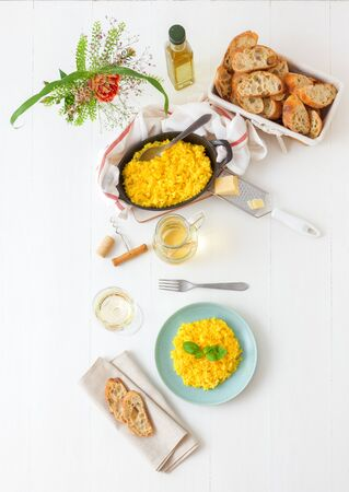 Risotto Milanese, wooden table with traditional Italian saffron risotto, glasses and pitcher of wine, bottle of olive oil, basket of bread and flowers. Top down view. Standard-Bild