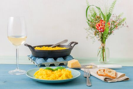 Risotto Milanese, wooden table with traditional Italian saffron risotto, glasses and pitcher of wine, bottle of olive oil, basket of bread and flowers.