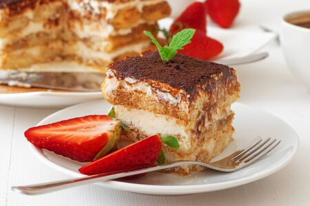 Tiramisu, homemade sweet Italian no bake dessert, cut of cake on small plate embellished with fresh mint and a few real strawberries, on white table. Whole cake and strawberries in background. Closeup Standard-Bild