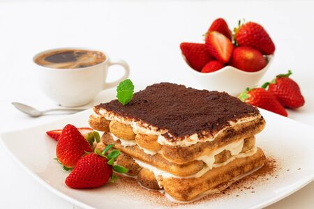 Tiramisu, homemade sweet Italian no bake dessert, cut of cake on small plate embellished with fresh mint and a few real strawberries, cup of coffee and bowl with strawberries on white table. Closeup.