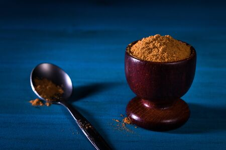 Ground cinnamon powder in wooden cup with small metal spoon on blue wooden table with dark background. Close up. This image or similar one has not been published yet.