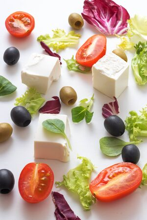 Greek salad, white Greek cheese, green and black olives, lettuce leaves, halfs of cherry tomato. White background. variations of salad leaves and feta myzithra cheese.