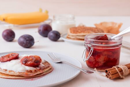 White wooden table with closeup image of dessert saucer with crumpets, pancakes, sour cream and fresh plums. The glass with cooked plums, fresh plums and fresh bananas in the background. 版權商用圖片